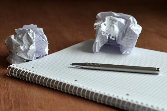 Vihko jonka päällä on kynä ja kaksi irtirevittyä, rytättyä sivua