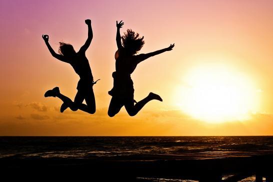 Kaksi siluettihahmoa hyppäämässä ilmaan laskevaa aurinkoa vasten.