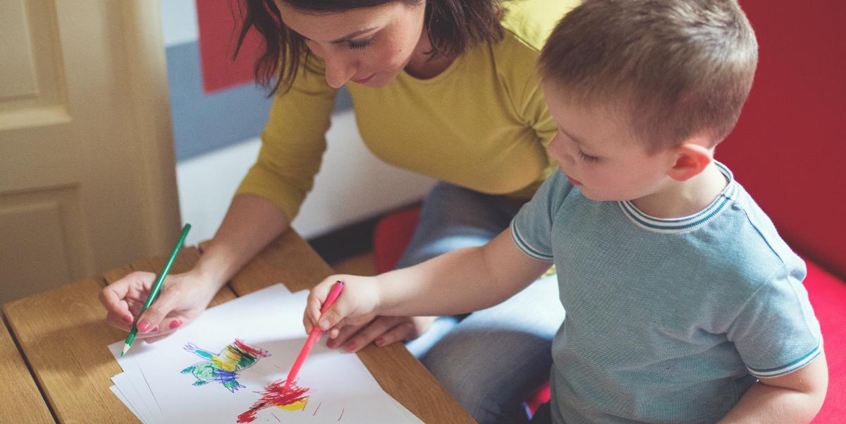 Ohjaaja ja lapsi piirtää