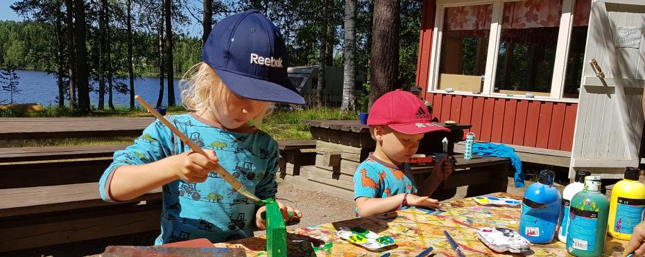Kaksi lasta ulkona maalaamassa.