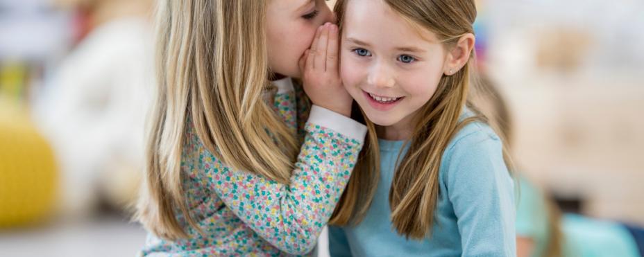 Lapsi kuiskaa jotain toisella lapselle