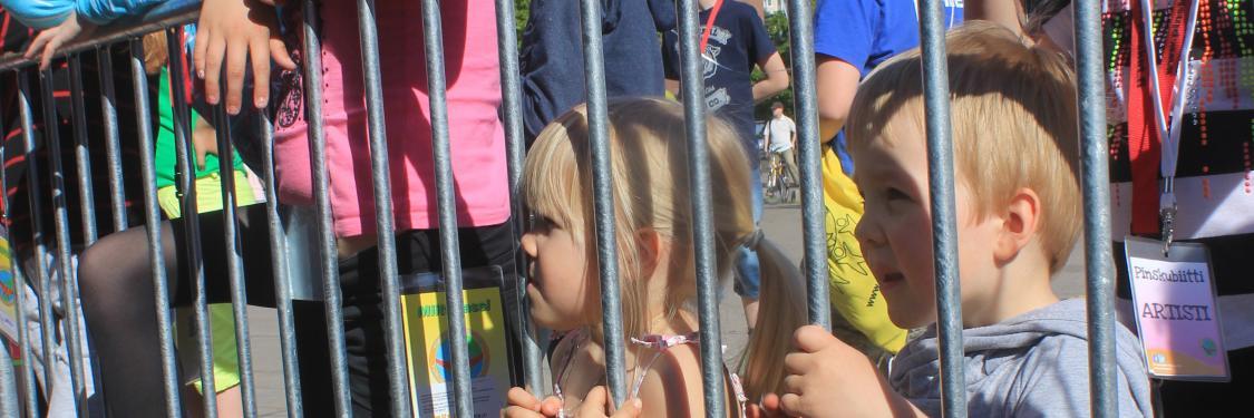 Kaksi lasta seisomassa festariaitaa vasten.